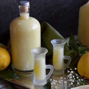 A large bottle with a few shot glasses of limoncello.