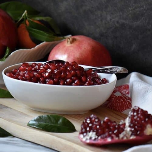 A bowl of ruby red pomegranate seeds.