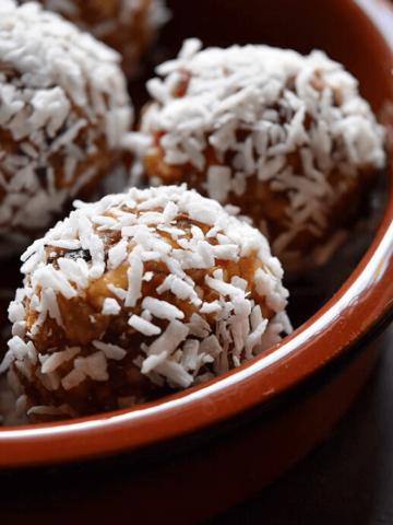 A bowl of shredded coconut covered Greek Yogurt Goji Berry Almond Date Energy Bites