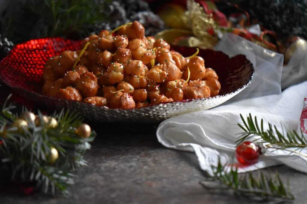 Italian honey balls in a red bowl.