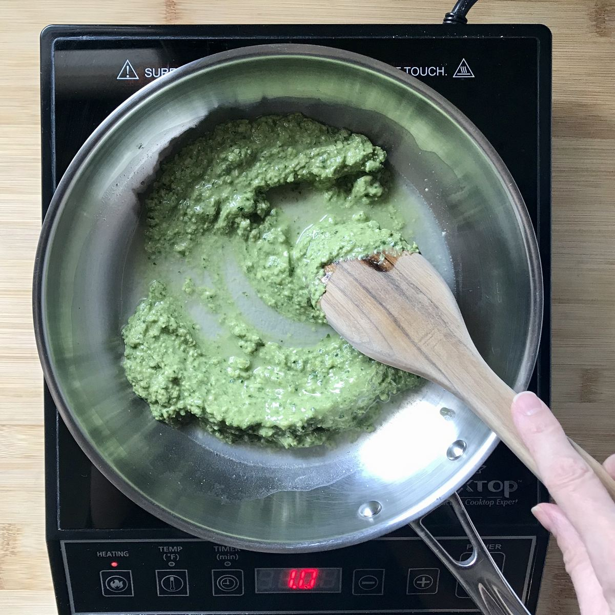 Pasta water is added to the pesto sauce in a pan.