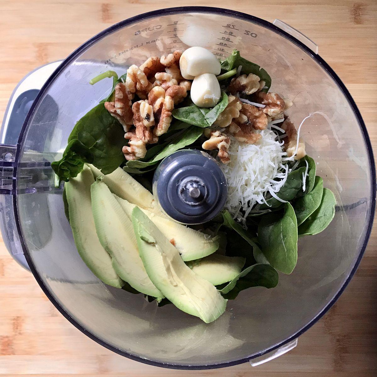 The ingredients for the Avocado Pesto Cavatelli Pasta Recipe are in a food processor.