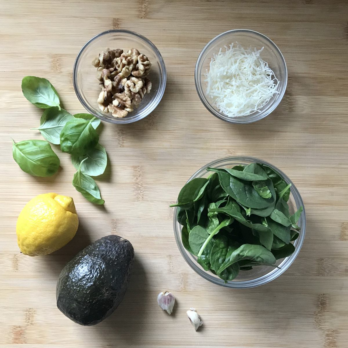 The ingredints to make the avocado pesto on a wooden board.