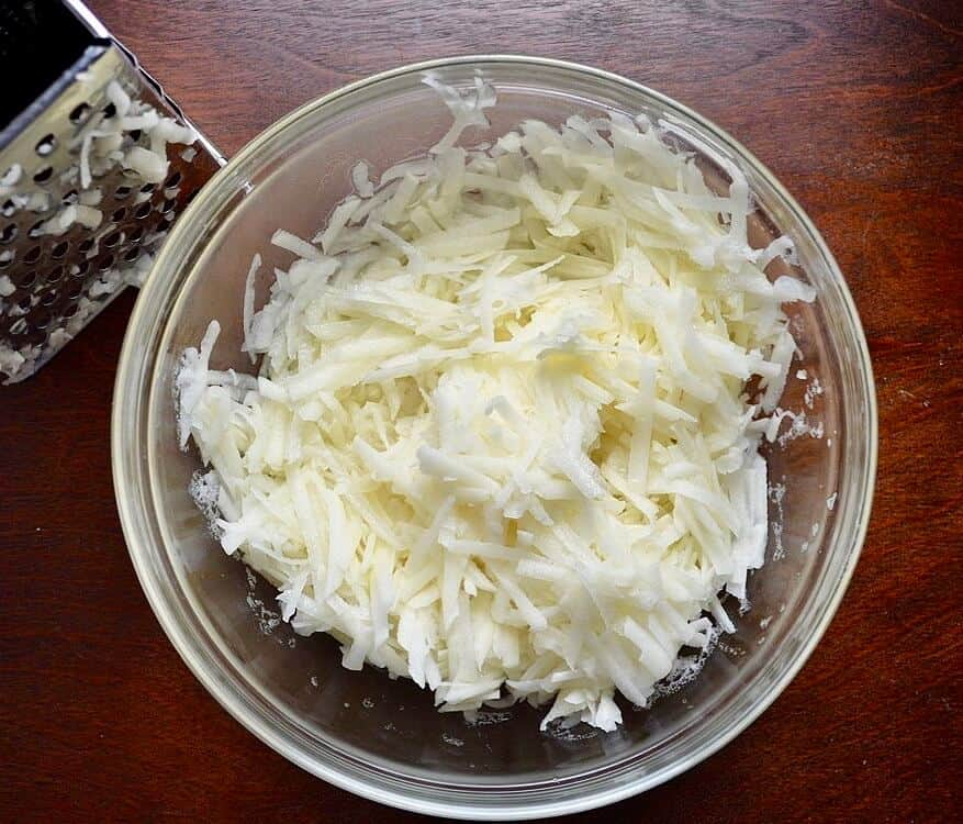 Freshly grated shredded potatoes in a glass bowl.