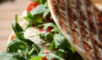 A Vegetarian Piadina Sandwich filled with arugula, tomatoes and mozzarella.