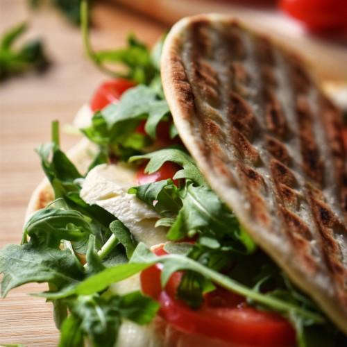 A Vegetarian Piadina Sandwich filled with arugula, tomatoes and mozzarella.