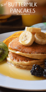 A stack of buttermilk pancakes topped with bananas.
