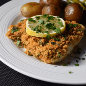 Oven baked cod fish on a white plate.