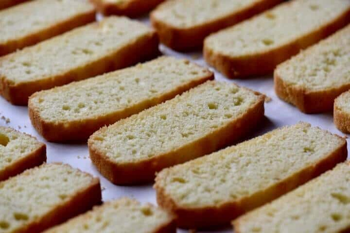 Sliced anise biscotti, all lined up on a baking tray, ready for the second bake.