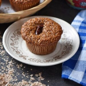 A close up shot of a bran muffin on a plate.