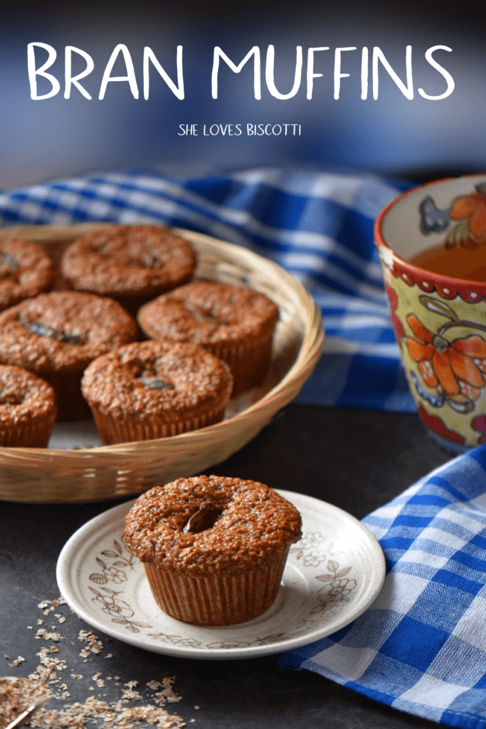 A bran muffin on a plate. In the background, a basket of muffins.