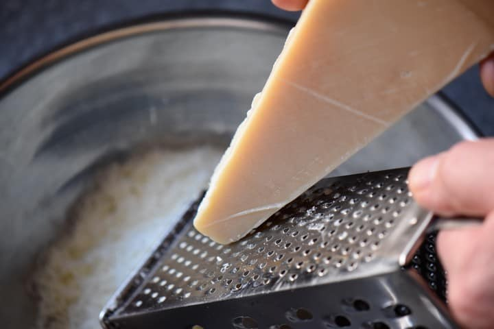 A box grater is used to grate Parmesan cheese for the crescia recipe.
