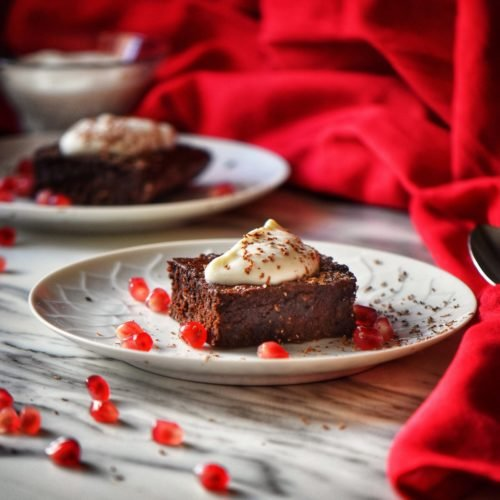 A close up shot of a square piece of Healthy Chocolate Brownie topped with whipped ricotta and surrounded with pomegranate arils.