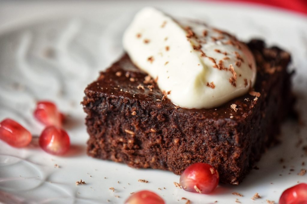 A piece of healthy chocolate brownie topped with ricotta.