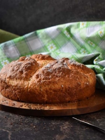 A freshly baked Irish soda bread placed on a round wooden board, ready to be sliced.