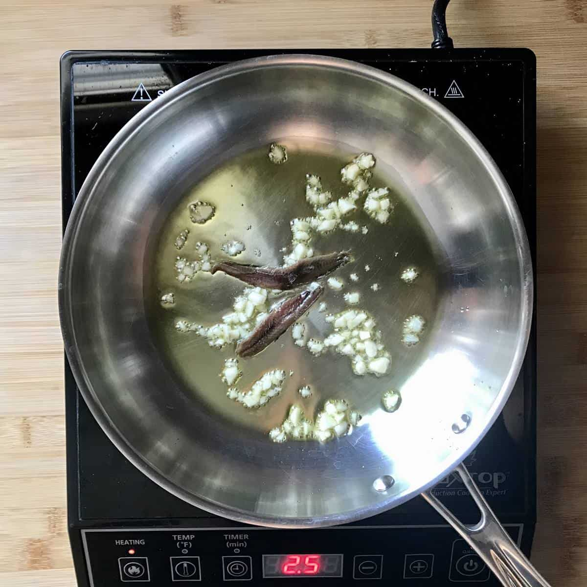Sauteed garlic and anchovies in a pan.