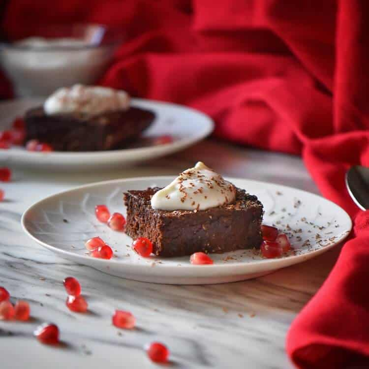 A piece of chocolate brownie served with pomegranate arils and whipped ricotta.