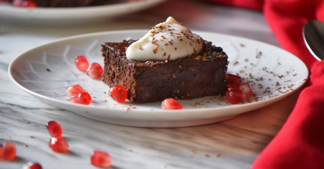A front view of a square piece of chocolate brownie on a white plate topped with a spoonful of whipped ricotta.