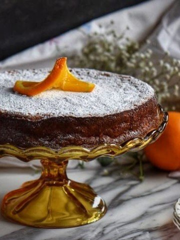 Rice ricotta Easter pie in a cake stand surrounded by oranges and lemons in the background.