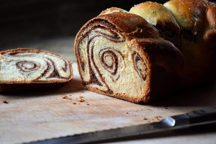 A freshly sliced loaf of cozonac is on a wooden board.