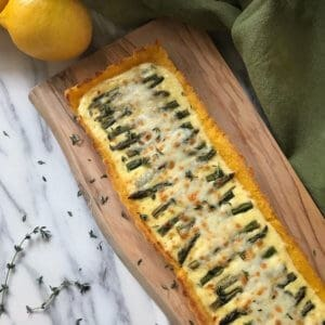 A square overhead image of the Asparagus Ricotta Tart on a wooden board.