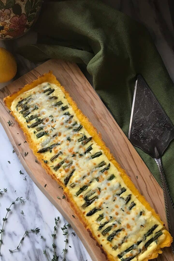 d shot of a baked Asparagus Ricotta Tart on a wooden cutting board.