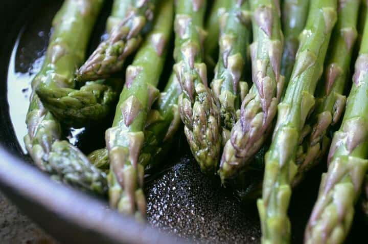 Asparagus tips shown in a cast iron pan being sautéed.