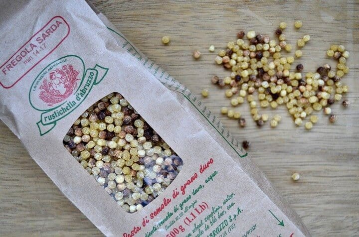 An overhead shot of the packaged fregola along with a handful of fregola on a wooden board.