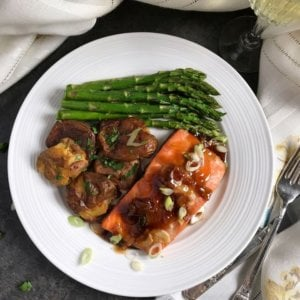 An overhead shot of a white dinner plate with glazed salmon, sauteed asparagus and smashed potatoes.