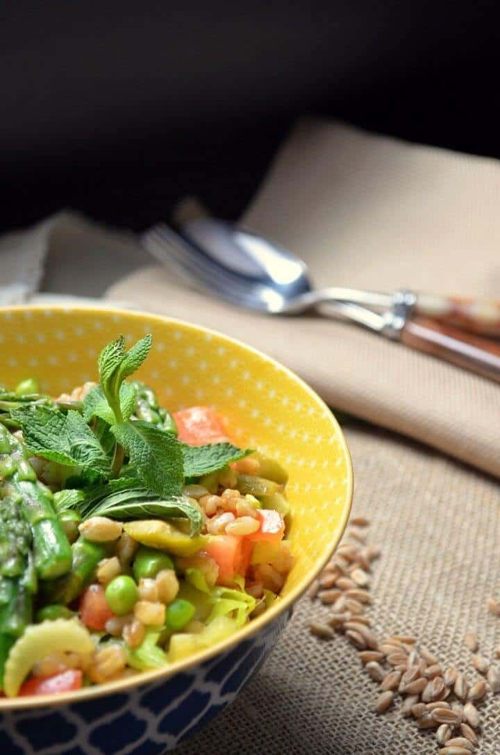A bowl of the pea farro salad along side a few scattered grains of farro.