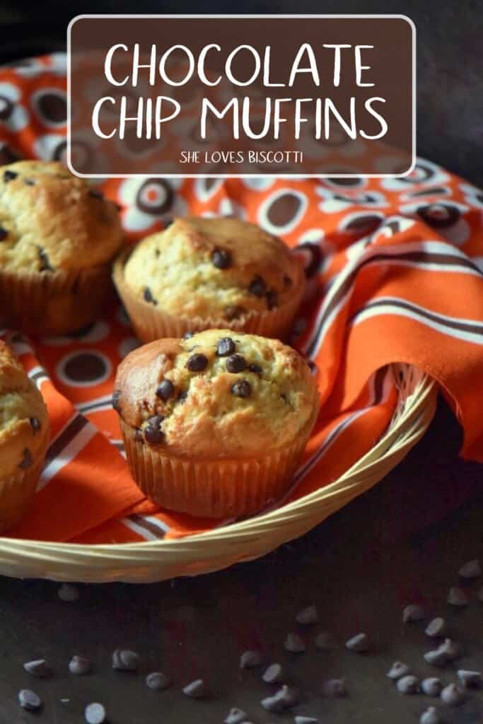 Chocolate chips scattered around a basket of chocolate chip muffins.