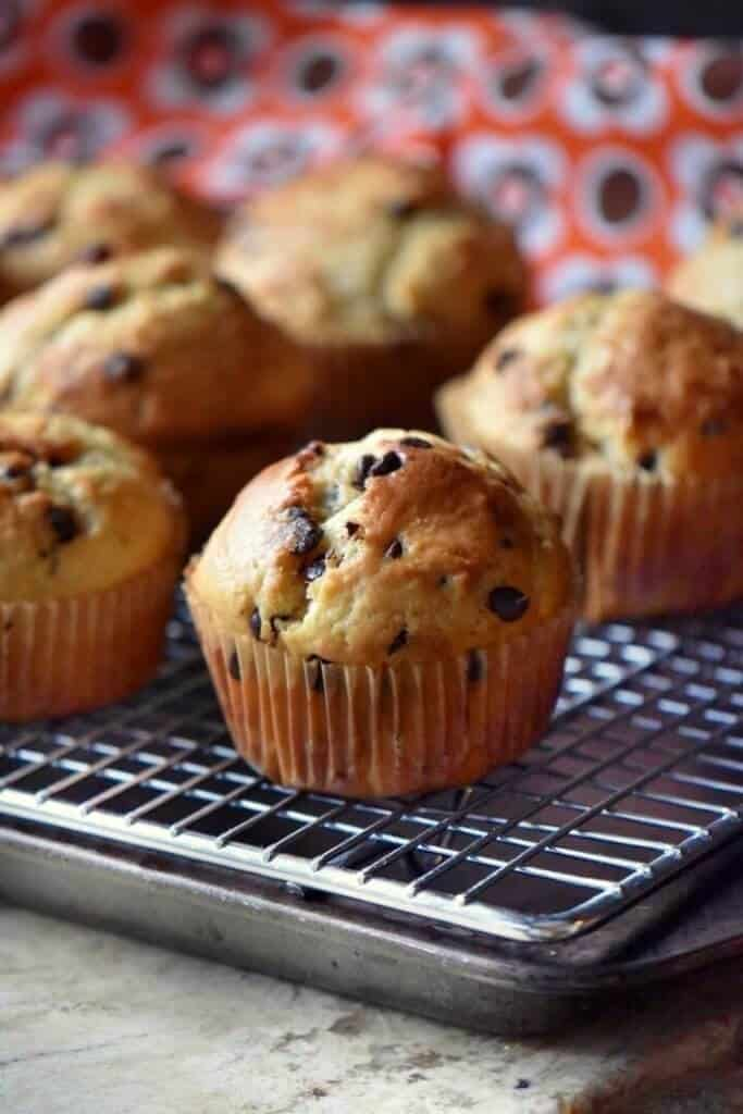 Bakery Style Chocolate Chip Muffins cooling off on a wire rack.