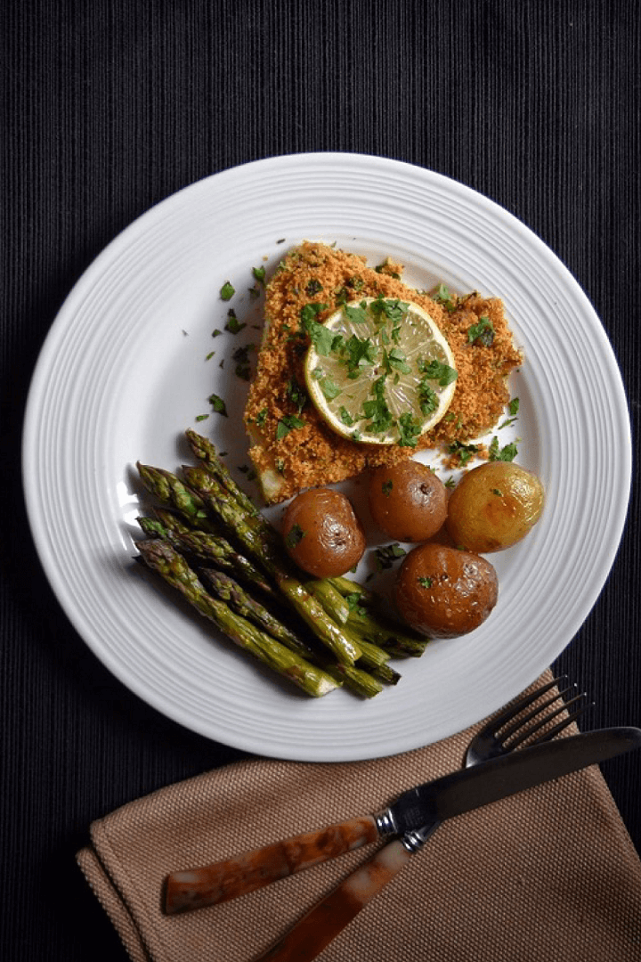 An overhead shot of the oven baked cod fish with asparagus and roasted potatoes.