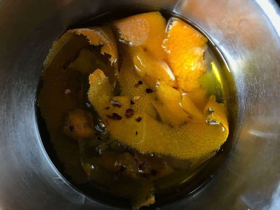 The infusion of the olive oil with orange zest in a small pot.