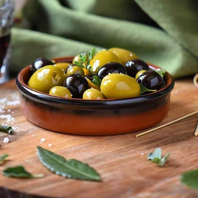 A close up shot of marinated olives in a brown terra cotta serving dish
