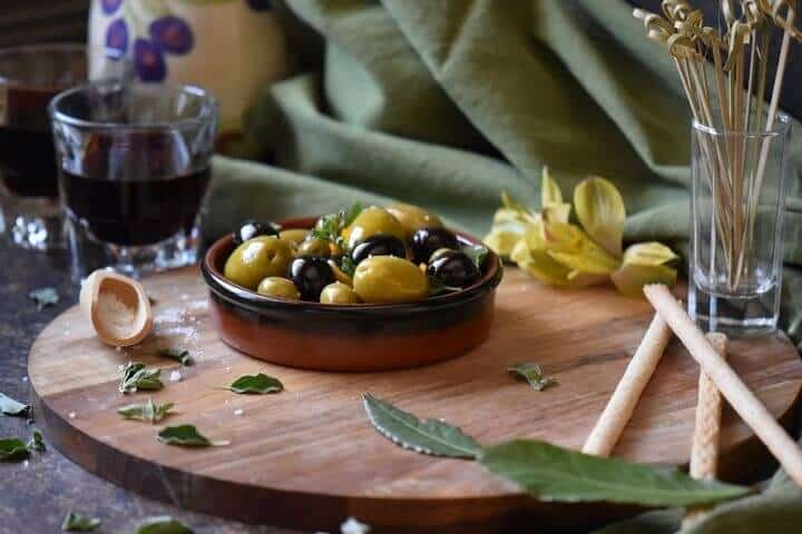 A round serving dish filled with black and green olives which have been marinated with olive oil and orange zest.