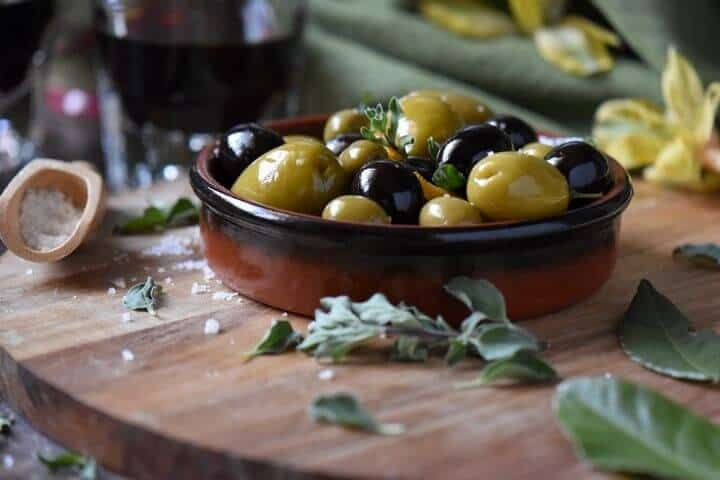Marinated olives, of the green and black variety in a small dish, surrounded by oregano and salt.