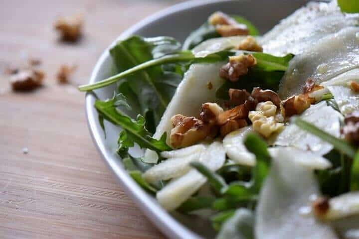 A close up of the arugula, pears and walnuts -just some of the ingredients used to make this salad.