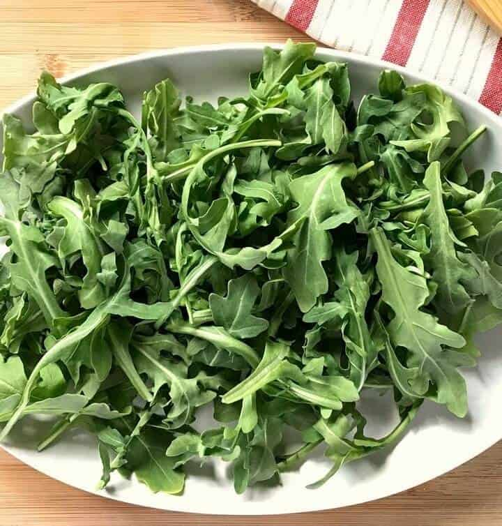 Arugula leaves scattered on a white oval plate.