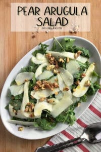 An overhead shot of an arugula salad with thin slices pf pear, parmesan cheese and toasted walnuts.