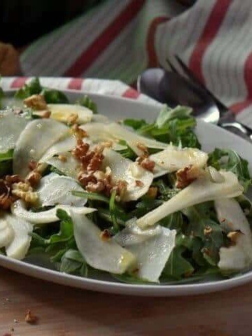 The pear arugula salad nicely arranged on a white oval platter.