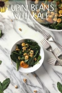 An overhead shot of a small portion and a big bowl of lupini beans salad with kale .