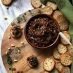 An overhead shot of eggplant caponata in a round dish, surrounded by sliced crispy baguette and scattered pine nuts.