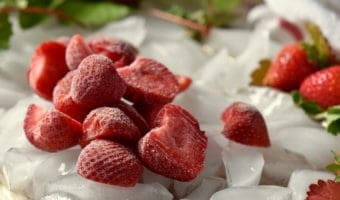 A close up of icy cold frozen strawberry halves set on ice.
