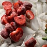 Frozen strawberries thawing on a bed of ice cubes.