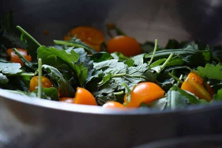 The combination of cherry tomatoes and baby kale in a salad bowl.