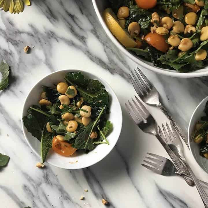 A small white salad bowl with lupini beans, baby kale and cherry tomatoes.