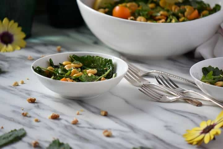 Scattered walnuts and kale leaves around a bowl of lupini salad.