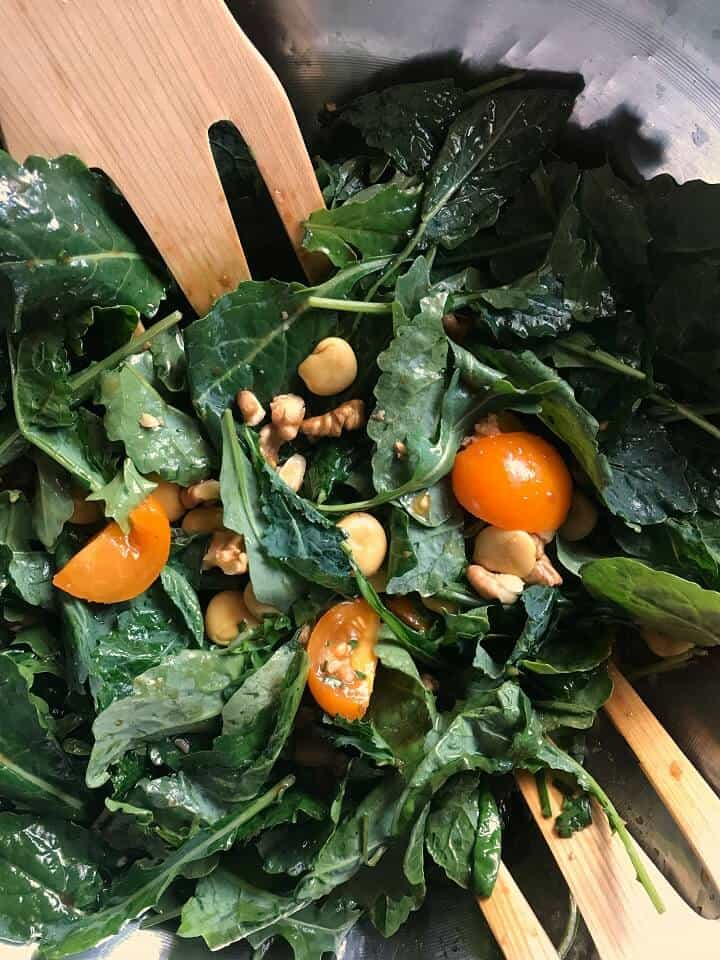 Lupini and kale being tossed together in a large salad bowl.