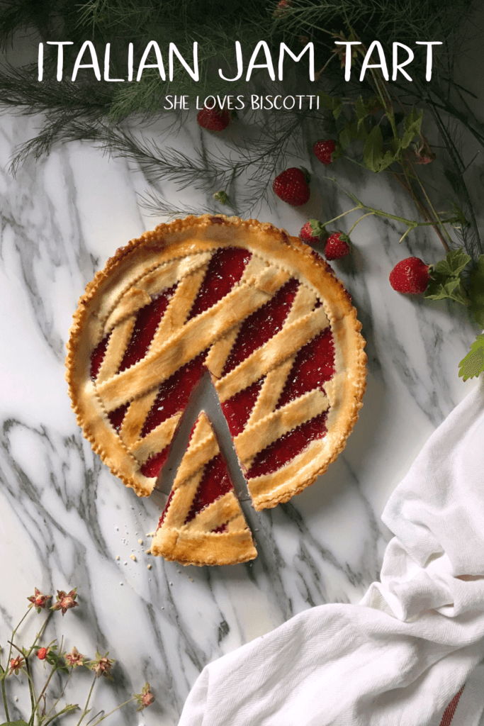 An overhead shot of the Italian Jam Crostata, surrounded by the green leaves of strawberry plants and a few strawberries.